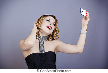 Young woman in evening outfit taking a selfie with her mobile phone