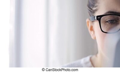 young woman in eyeglasses with tablet pc at home