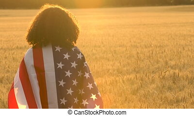 Young Woman in Field Wrapped in American Flag at Sunset or Sunrise