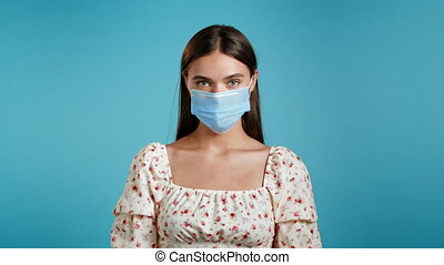 Young woman in floral dress and protective medical mask looking to camera. Portrait of beautiful girl on blue wall studio background. Quarantine, pandemic concept.