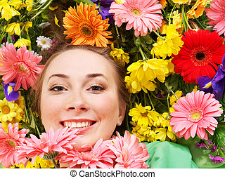 Young woman in flowers touching face.