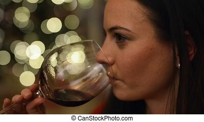 Young woman in front of Christmas tree drinking wine.