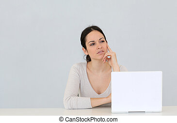 Young woman in front of laptop computer isolated