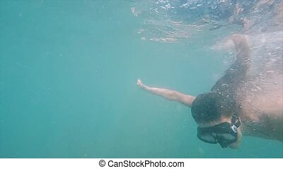 Young woman in full-face mask dives into water. Snorkeling in tropical sea, active vacation. Slow motion.