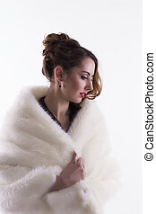 Young woman in fur coat on a white background