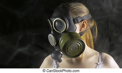 Young woman in gas mask among smoke