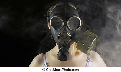 Young woman in gas mask and smoke