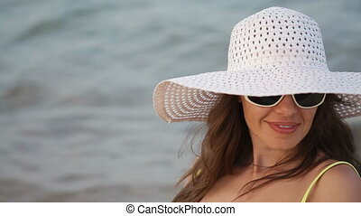 young woman in glasses and a hat on a beach near the sea