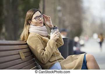 Young woman in glasses at park drinking coffee