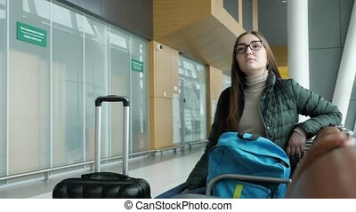 Young woman in glasses is waiting her flight in airport sitting in hall.