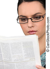 Young woman in glasses reading a newspaper
