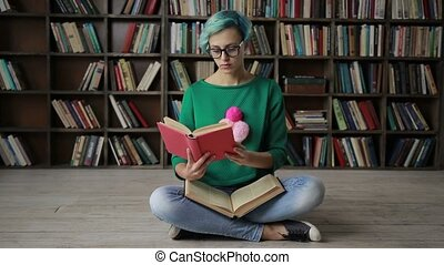 Young woman in glasses reading an interesting book -...