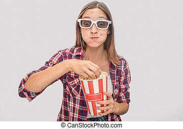 Young woman in glasses standing and watching straight. She eats popcorn and has box of it in hands. She blew chicks. Model is satisfied. Isolated on grey background.