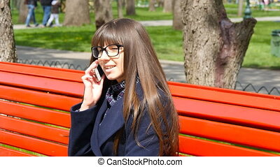 Young woman in glasses talking on the mobil phone in a city park. Girl sitting on a red bench outdoor in spring and speaking on smartphone. Close-up