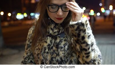 Young woman in glasses using smartphone on night city lights...