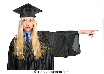 Young woman in graduation gown pointing on copy space