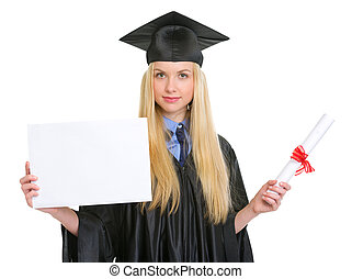 Young woman in graduation gown with diploma showing blank billboard