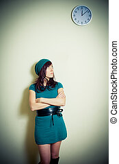 Young woman in green dress waiting and looking up at wall clock