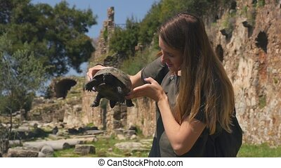 Young woman in green t-shirt holding in hands old tortoise