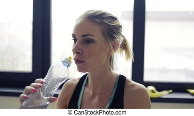Young woman in gym resting, holding bottle, drinking water....