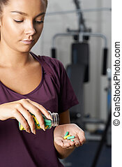 Young Woman In Gym Taking Tablets