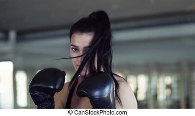 Young woman in gym with boxing gloves doing exercise indoors.