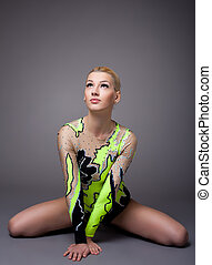 Young woman in gymnast suit posing on grey