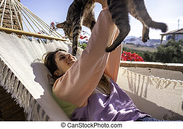 Young woman in hammock with her cat
