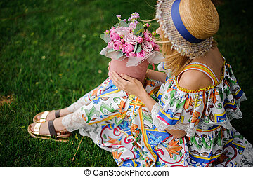 young woman in hat and colorful dress sits on lawn with bouquet