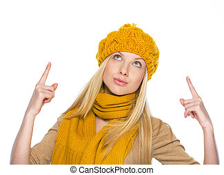 Young woman in hat and scarf pointing up on copy space
