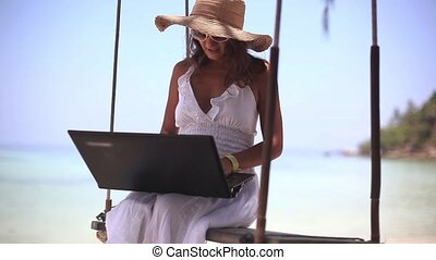 Young woman in hat and sunglasses working on the laptop sits...