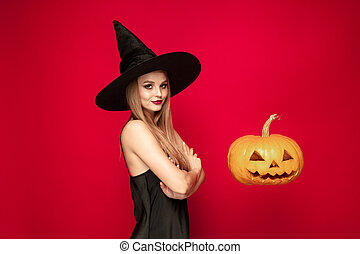 Young woman in hat as a witch on red background