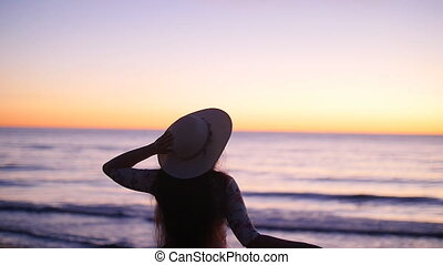 Young woman in hat at sunset near the sea. Concept of vacation
