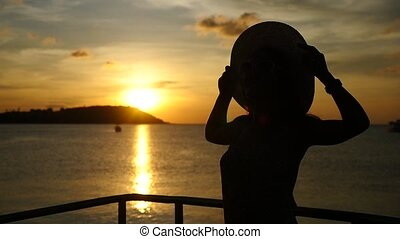 Young woman in hat enjoying sea cruise at amazing sunset. Thailand. Slow Motion.