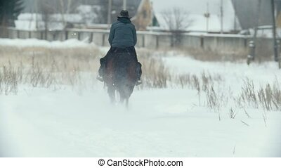Young woman in hat galloping on snow - slow-motion shot