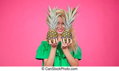 Young woman in hat holding a pineapple on a pink background...