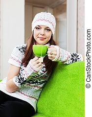 woman in hat warms with cup of tea