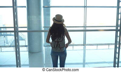 Young woman in hat with backpack coming to window in terminal of airport and looking at runway. Girl waiting for her airplane. Tourism and travel concept. Rear back view Slow motion