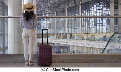 Young woman in hat with baggage in international airport walking with her luggage. Airline passenger in an airport lounge waiting for flight aircraft