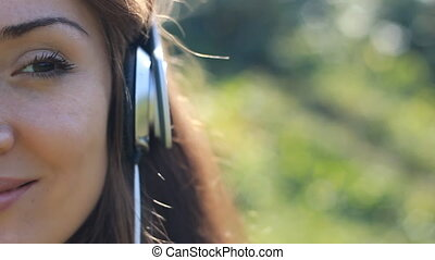 Young woman in headphones listens to music. Portrait closeup