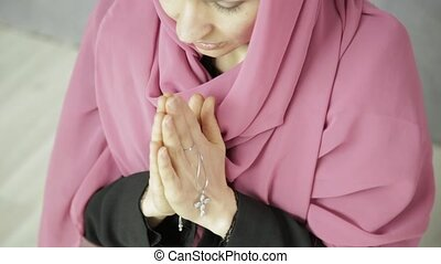 young woman in headscarf is praying. close-up female hands holding chain with a cross