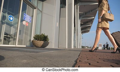Young woman in heels walking with her suitcase to entrance of airport. Business lady going to the airport with her luggage. Girl roll suitcase on wheels. Trip or vacation travel concept. Slow motion