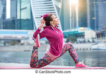 Young woman in Horse rider pose against the skyscrapers