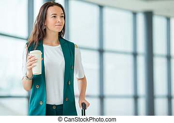 Young woman in international airport walking with her luggage and coffee to go
