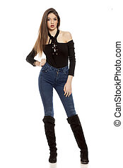 young woman in jeans and leather boots