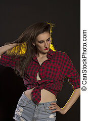 Young woman in jeans shorts and red checked shirt