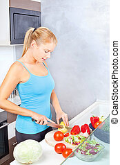 Young woman in kitchen cutting vegetables