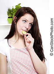 young woman in kitchen nibbling on a cucumber looking to side
