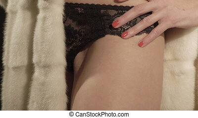 Young woman in lingerie and fur coat posing. Part of a female body closeup