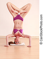 Young woman in lingerie doing a headstand with legs crossed